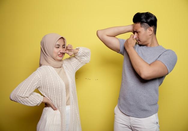 Dois jovens casal cheiram corpos malcheirosos. e segurando o nariz isolado em uma parede amarela