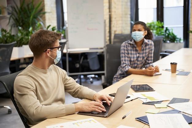 Dois jovens colegas de trabalho usando máscaras médicas de proteção sentados juntos à mesa no moderno