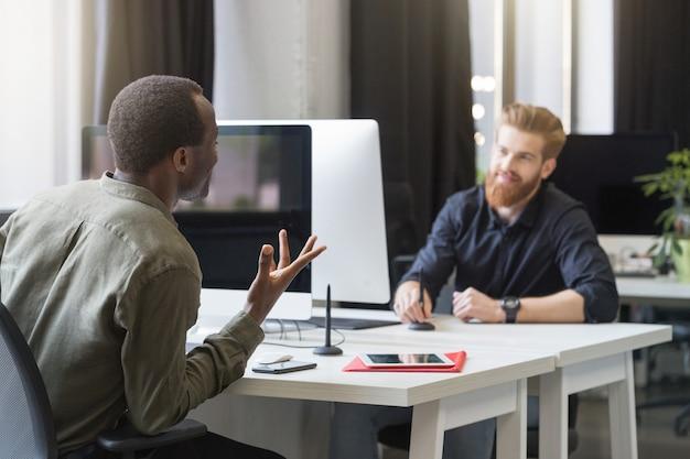 Dois jovens colegas masculinos, sentado em mesas opostas