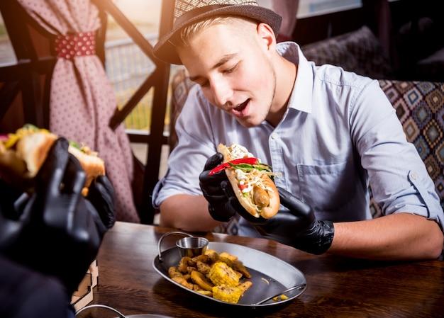 Dois jovens com fome comendo cachorro-quente no café. restaurante