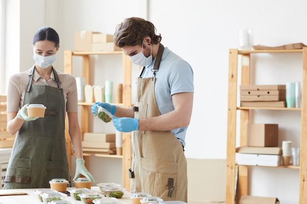Dois jovens com máscaras protetoras e luvas trabalhando juntos em serviço de entrega de comida