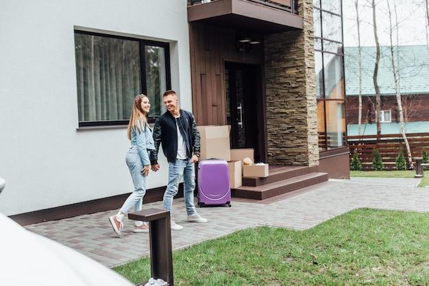 Dois jovens comprando nova casa moderna e movendo-se para este lugar.