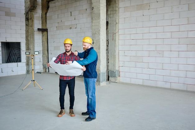 Dois jovens construtores com capacetes de proteção discutindo o esboço na planta enquanto apontam a estrutura principal na reunião inicial