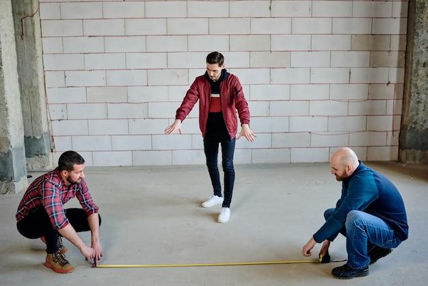 Dois jovens construtores sentados em agachamentos segurando pontas de fita métrica no chão e seu capataz os consultando durante o trabalho