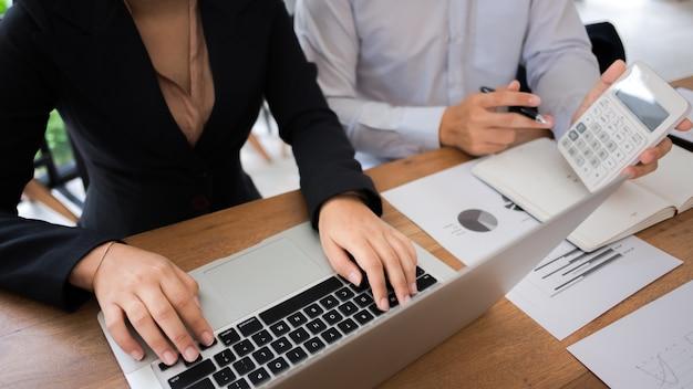 Dois jovens consultor de parceiros de negócios que trabalham com calculadora no investimento em avaliação de recursos de dados