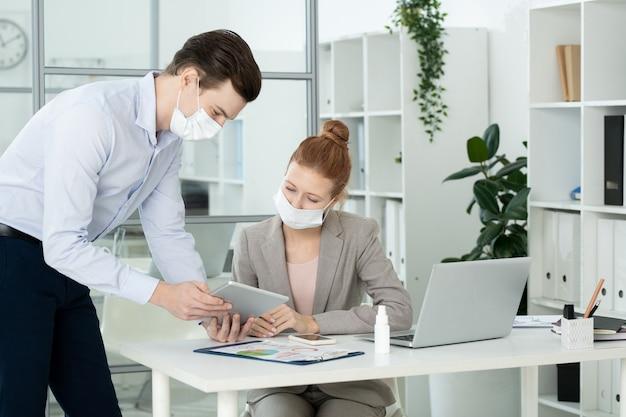 Dois jovens contadores elegantes com máscaras protetoras discutindo dados financeiros na tela do tablet durante a apresentação no local de trabalho no escritório