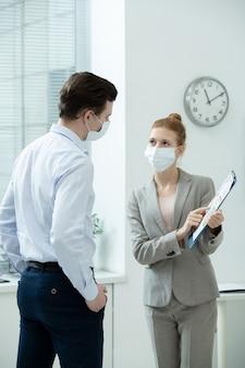 Dois jovens contadores elegantes com máscaras protetoras discutindo documentos financeiros com diagramas e gráficos em reunião de trabalho no escritório