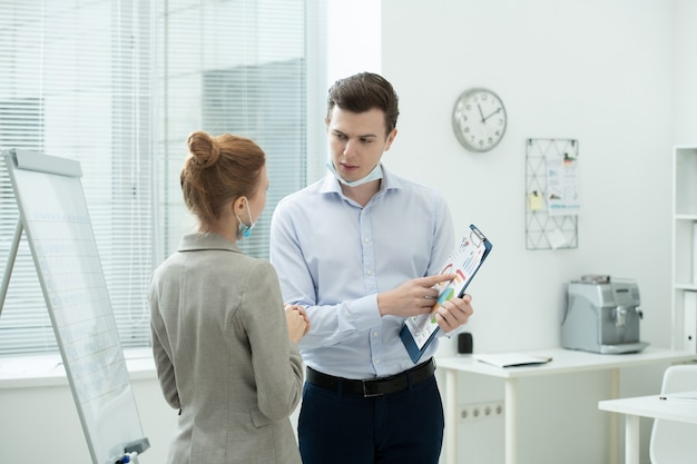 Dois jovens contadores elegantes discutindo dados financeiros em um documento com diagramas e gráficos enquanto um homem aponta para o papel no escritório