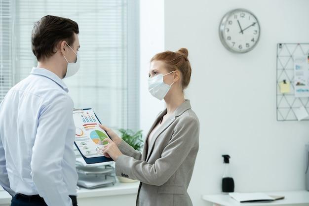 Dois jovens contadores elegantes usando máscaras protetoras discutindo dados financeiros em documentos com diagramas e gráficos em reunião no escritório
