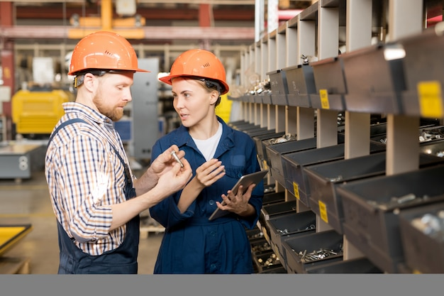 Dois jovens controladores confiantes em capacetes e uniformes verificando a qualidade das peças de reposição antes do processo de construção