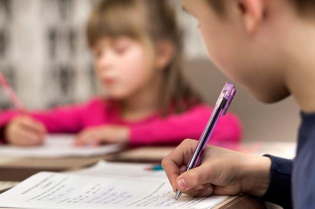 Dois jovens crianças bonitos, menino e menina, irmão e irmã fazendo lição de casa, escrevendo e desenhando em casa. arte educação, criatividade e crianças atividades conceito.