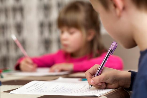 Dois jovens crianças bonitos, menino e menina, irmão e irmã fazendo lição de casa, escrevendo e desenhando em casa na turva.