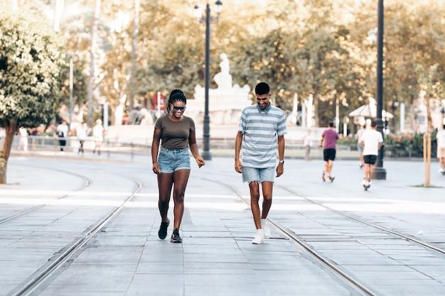 Dois jovens de diferentes etnias sorrindo enquanto caminham por uma cidade. sevilha, espanha