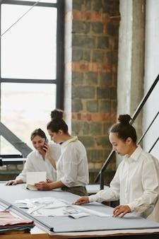 Dois jovens designers de roupas ligando para um dos clientes sobre o pedido, enquanto seu colega mede comprimentos de padrões de papel nas proximidades