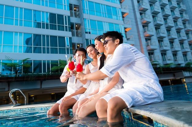 Dois jovens e bonitos casais asiáticos ou amigos chineses bebendo coquetéis em um luxuoso e sofisticado bar na piscina de hotel