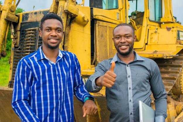 Dois jovens e bonitos empreiteiros africanos sentindo-se oprimidos ao ficarem ao lado de um trator fazendo sinal de positivo