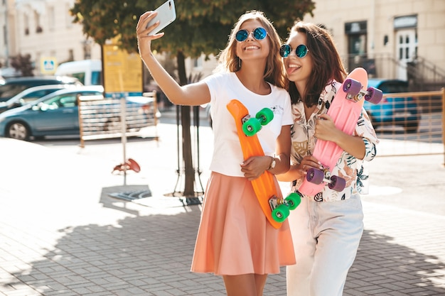 Dois jovens elegantes morena hippie morena e mulheres loiras. modelos em dia ensolarado de verão em roupas hipster, tirando fotos de selfie para mídias sociais no telefone. com caneta colorida