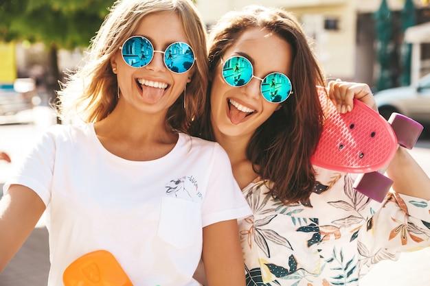 Dois jovens elegantes sorrindo morena hippie em dia ensolarado de verão em roupas hipster com posando de skate centavo