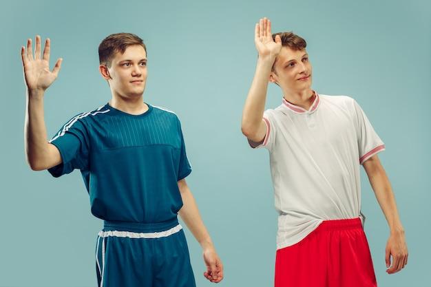 Dois jovens em pé e cumprimentando em roupas esportivas isoladas em azul