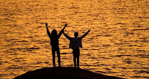 Dois jovens em pé na rocha em frente à água com as mãos ao alto, olhando para o pôr do sol