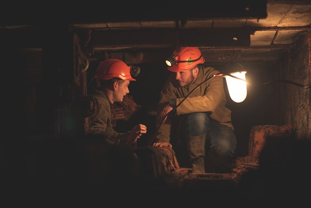 Dois jovens em roupas e capacetes especiais, trabalhando na mina