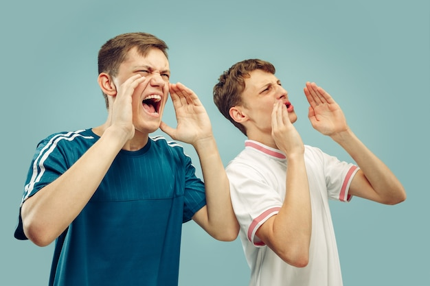 Dois jovens em roupas esportivas isoladas em azul