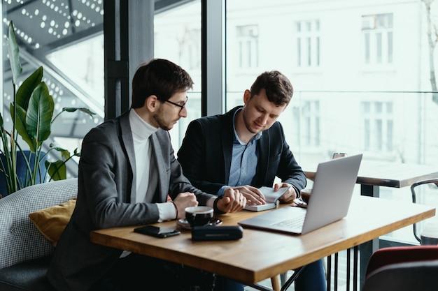 Dois jovens empresário tendo uma reunião bem sucedida no restaurante.