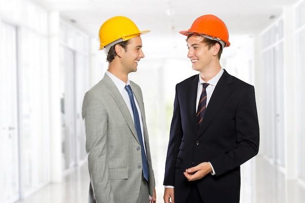Dois jovens empresário usando capacete de segurança
