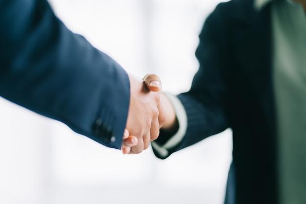 Dois jovens empresários asiáticos apertam as mãos após assinar um contrato