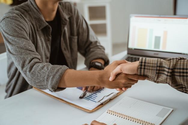 Dois jovens empresários asiáticos apertaram as mãos de acordo