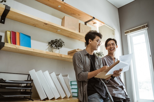 Dois jovens empresários asiáticos conversando sobre suas análises de produtos
