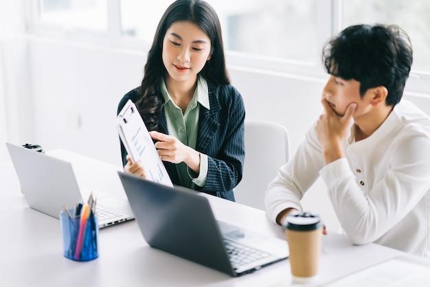 Dois jovens empresários asiáticos discutem projeto de fim de ano