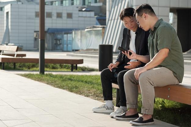 Dois jovens empresários chineses olhando para a tela do smartphone