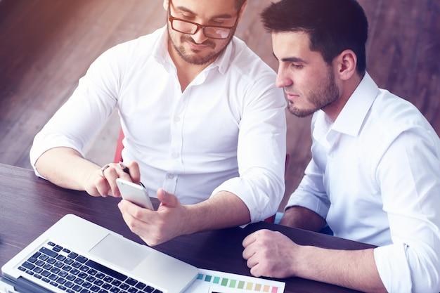 Dois jovens empresários trabalhando em um laptop em um escritório moderno. efeito de filme, reflexo de lente