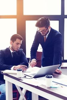 Dois jovens empresários trabalhando no laptop em um escritório moderno. homens de negócios hipster de barba. efeito de filme, reflexo de lente