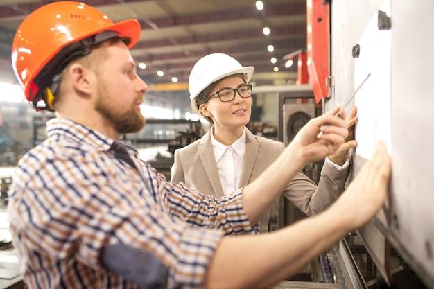 Dois jovens engenheiros confiantes de capacetes, olhando para um desenho, enquanto um deles aponta para um papel no quadro branco