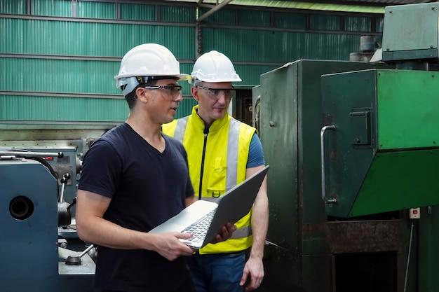 Dois jovens engenheiros estão projetando e fabricando peças de automóveis em uma fábrica na tailândia.