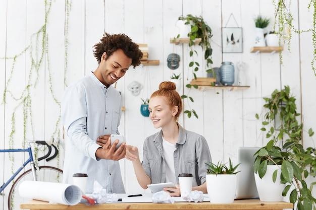 Dois jovens engenheiros ou arquitetos usando dispositivos eletrônicos durante uma pequena pausa no escritório