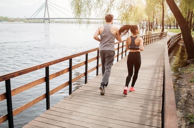 Dois jovens estão correndo na ponte perto do rio.
