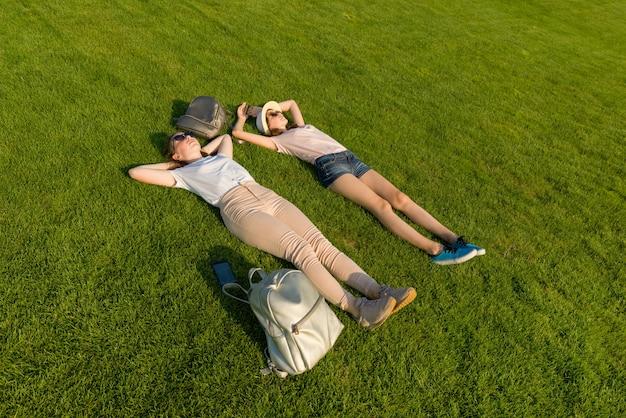 Dois jovens estudantes do sexo feminino com mochilas deitado na grama verde.