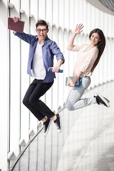 Dois jovens estudantes felizes pulando na faculdade.