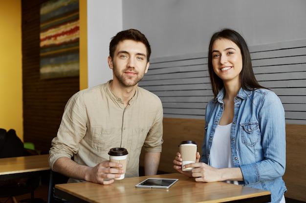 Dois jovens estudantes lindos sentado na cafeteria, bebendo chocolate, sorrindo, posando para o artigo de jornal da universidade