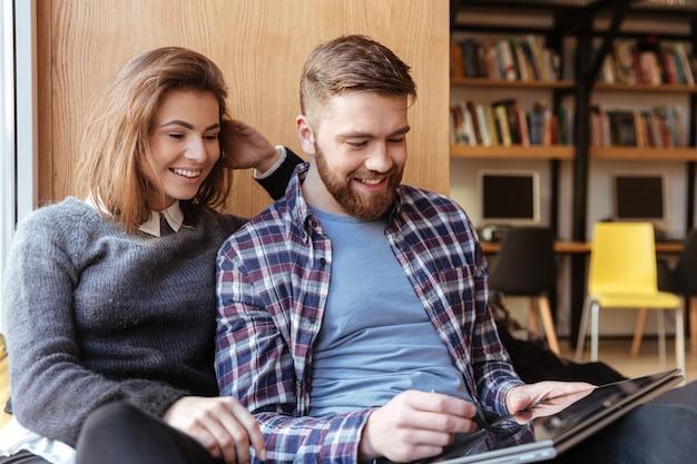Dois jovens estudantes usando computador tablet