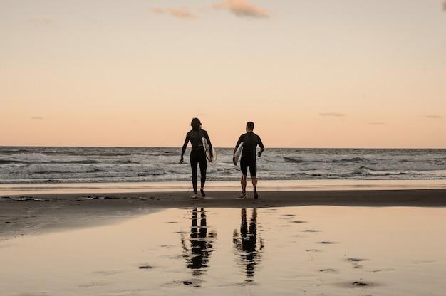 Dois jovens fisicamente aptos, andando em roupas de mergulho pretas com pranchas, caminhando para o mar ao entardecer
