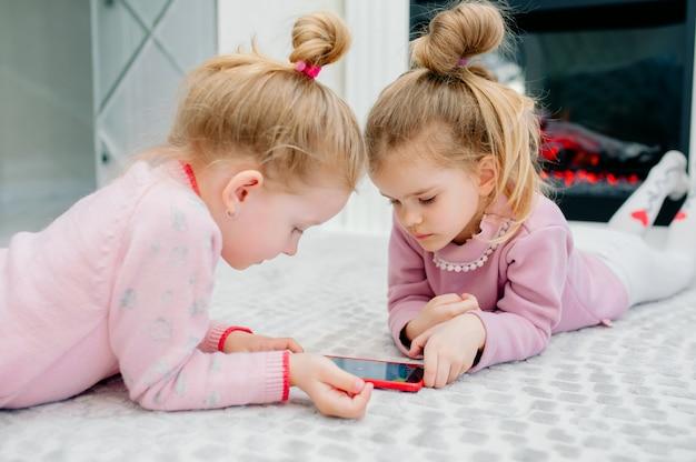 Dois jovens focados crianças jogando um smartphone sem nome deitado no chão da sala. crianças pequenas e tecnologia, irmãs brincam com um telefone celular, assistem a vídeos ou jogam jogos