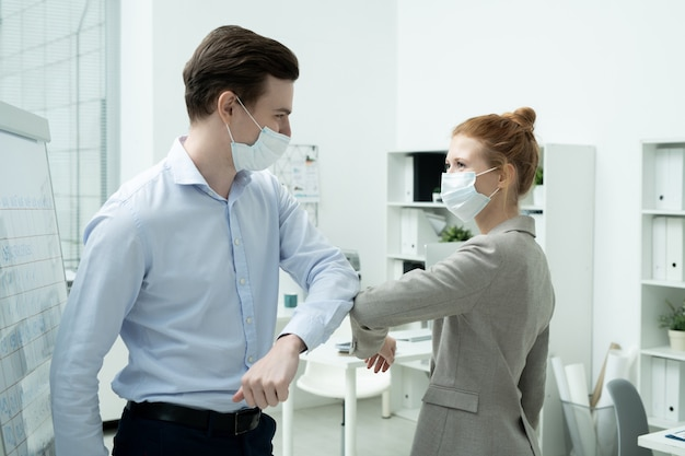 Dois jovens gerentes de escritório felizes em trajes formais e máscaras protetoras se dando cotoveladas em vez de um aperto de mão ou abraço
