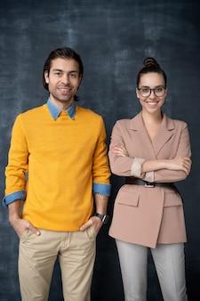 Dois jovens gerentes de escritório ou profissionais de negócios em trajes casuais elegantes, sorrindo, parados na frente da câmera