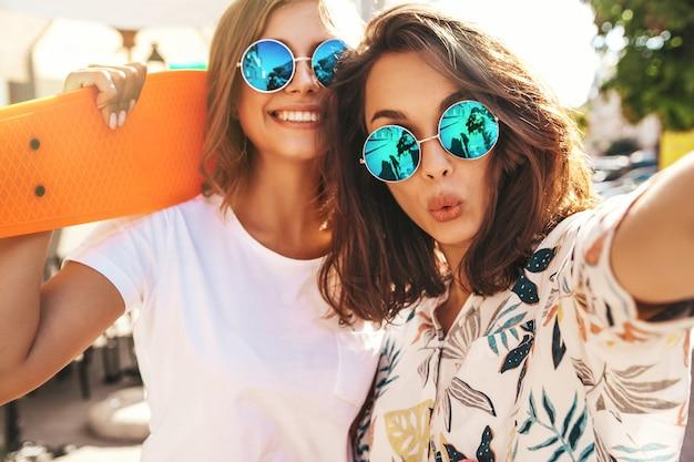 Dois jovens hippie elegante feminino morena e loiras mulheres em roupas de verão hipster tomando selfie