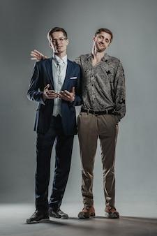 Dois jovens iguais em idade homens vestidos diferentemente posando juntos.