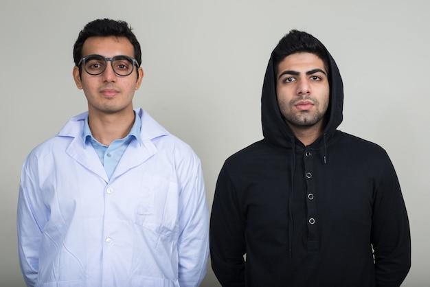 Dois jovens indianos como médico e paciente juntos contra uma parede branca